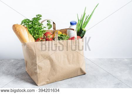 Paper Shopping Box Full Of Fresh Organic Vegetables And Grocery Products On Grey Table. Eco-shopping