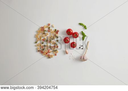 Whole Grain Colorful Pasta With Letter Shape Isolated On White Background With Tomatoes, Sea Salt, G