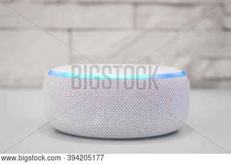 Amazon echo dot , Alexa voice controlled speaker with activated voice recognition, on brick and white background