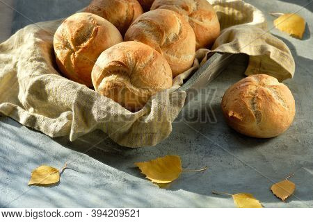 Kaiser, Or Vienna Buns In Bread Basket On Dark Grey Background With Yellow Autumn Leaves.