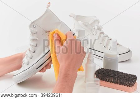 Man Removing A Spot Of Dirt From A White Canvas Sneaker