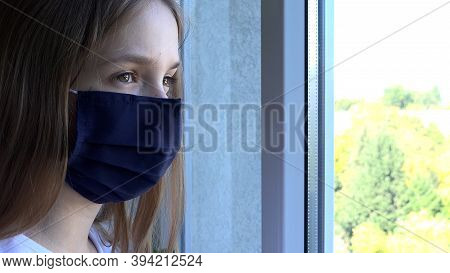 Sick Girl Wearing Protective Mask In Coronavirus Pandemic, Sad Child Looking On Window, Unhappy Bore