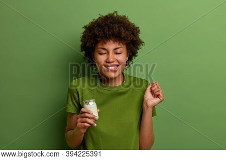 Pleased Curly Haired Woman Imagines Taste Of Delicious Fresh Yoghurt, Clenches Fist And Bites Lips A