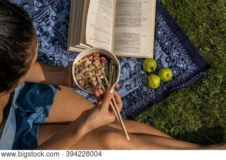 Young Woman Relaxing Having A Picnic Outdoor Sitting On Blanket On Grass And Eating Takeout Food Wit