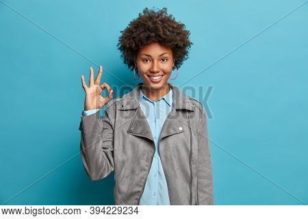 Confident Self Assured Woman Shows Okay Sign Or All Right Gesture, Recommends Good Product And Smile