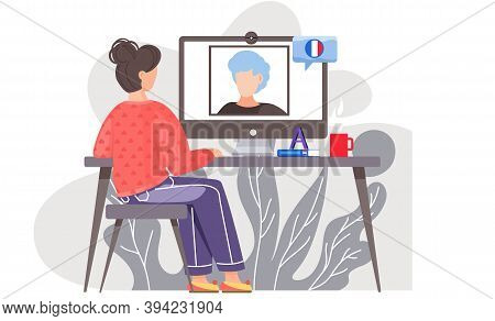 A Girl Sits In Front Of A Computer Monitor At Lesson In French With Native Speaker. The Teacher On S