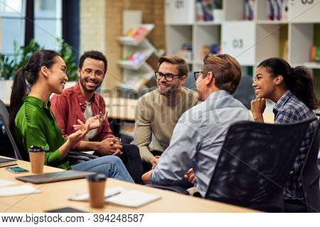 Creating Success. Group Of Young Happy Multi Racial Business People Communicating And Sharing Ideas