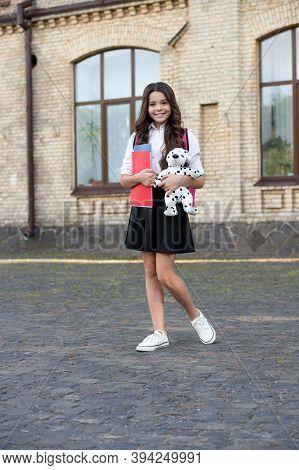 Happy Small Kid In School Uniform Hold Books And Toy Dog In Schoolyard, Homework Club.