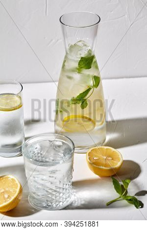 drink, detox and diet concept - glasses with fruit water or lemonade, lemons and peppermint on white table