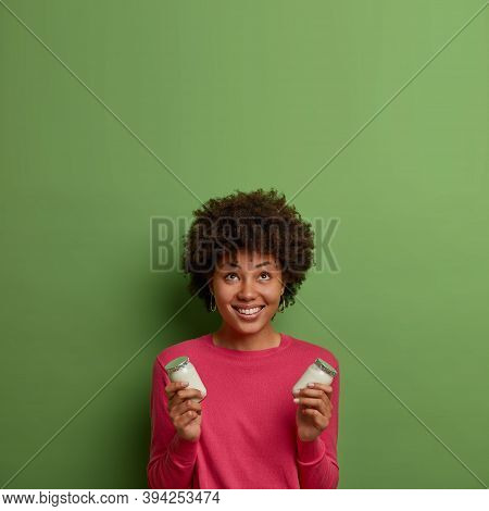 Vertical Shot Of Curly Positive Woman Looks Above With Smile, Holds Delicious White Organic Yoghurt,