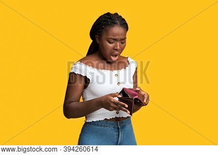 Poverty And Absence Of Money. Shocked African American Woman Checking Empty Wallet, Frustrated Black