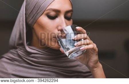 Portrait Of Arab Woman Drinking Water From Glass Standing In Kitchen Indoors, Wearing Hijab Headscar