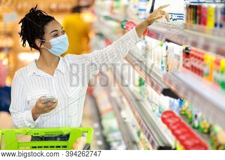 Grocery Shopping. African American Woman Wearing Protective Face Mask In Supermarket, Buying Food Pr