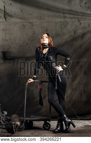 Young Woman In A Black Corset And With Leather Harnesses On Black  Background.  Sexual Bdsm Toy.   L