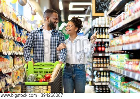 African Family Couple Shopping In Supermarket Buying Groceries And Choosing Food Walking With Shop C