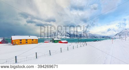 Norwegian Architecture And Winter Scenery With Colorful Wooden Houses In Small Fishing Village On Lo