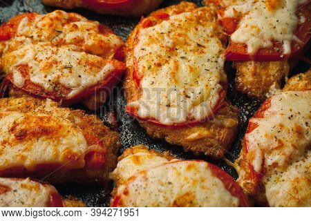Baked Chicken Fillet With Cheese And Tomato On A Baking Tray For Roasting. Meat Dish For The Festive