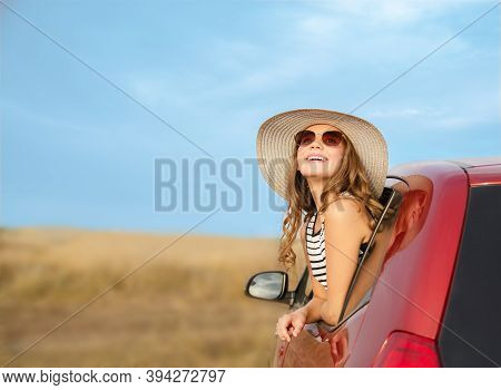 Cute Happy Smiling Little Girl Child Goes To Summer Travel Trip In The Red Car. Preteen In Hat And S
