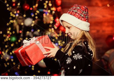 Girl Cute Child Hold Wrapped Gift Near Christmas Tree. Winter Shopping. Holiday Party That Actually