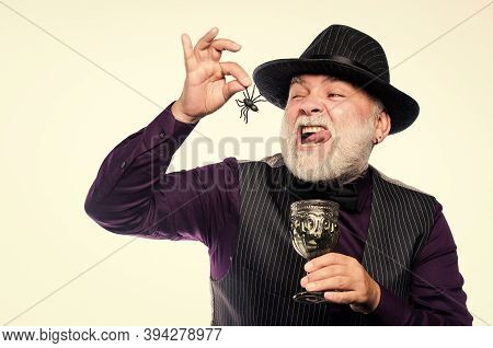 Halloween Party. Weird Old Grandfather With Gray Beard Eating Spider. Exotic Food. Disgusting Hallow