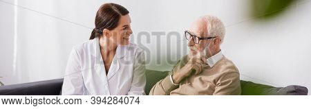 Nurse And Aged Man Talking While Sitting On Sofa At Home, Banner