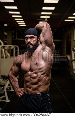 Strong Bearded Male In Bandana Showing Perfect Sport Physique With Abdominal Oblique Muscle In Dark
