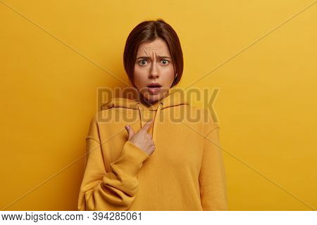 Perplexed Indignant Young Woman Points At Herself, Verbally Defenses And Looks With Embarrassement A