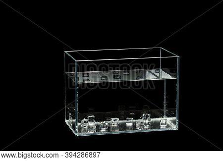 Glass Aquarium Isolated On Black Background. Ice Cubes In The Aquarium. Rectangle Aquarium Glass