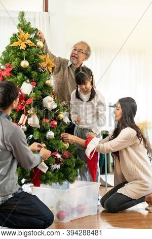 Multigenerational asian Family decorating a Christmas tree. Mom Dad daughter girl and grandfather decorate the Christmas tree prepare for season greeting of Merry Christmas and Happy Holidays.