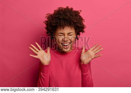 People And Joy Concept. Positive Curly Woman Laughs Happily, Raises Palms, Hears Hilarious Joke, Squ
