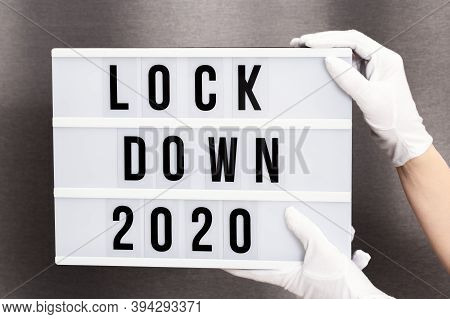Hands In White Gloves Hold Light Box With Message Lockdown 2020. Word Of The Year 2020 Is Lockdown.