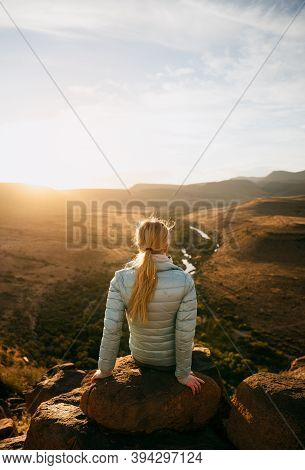 Free-spirited Young Teen Sitting Relaxing On Boulder On Top On Luscious Mountain Watching Sunset