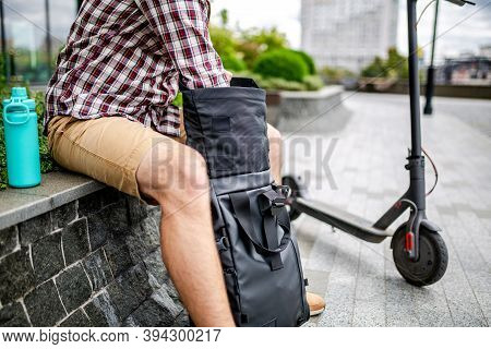 Young Caucasian Man Opens A Black Roll Top Backpack While Sitting On A Bench Near An Electric Scoote