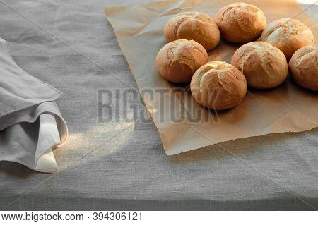 Kaiser Or Vienna Buns On Table Covered With Beige Linen Tablecloth.