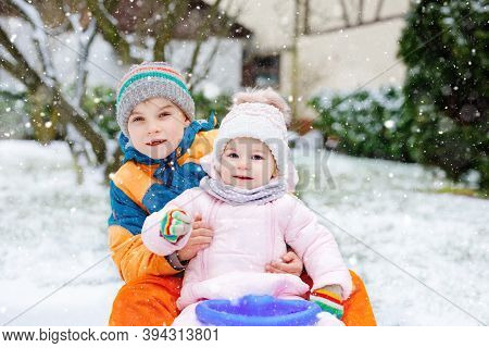 Little Kid Boy And Cute Toddler Girl Sitting Together On Sledge. Siblings, Brother And Baby Sister E