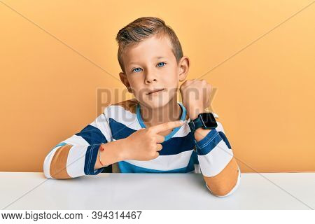 Adorable caucasian kid wearing casual clothes sitting on the table in hurry pointing to watch time, impatience, looking at the camera with relaxed expression