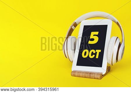 October 5th. Day 5 Of Month, Calendar Date. Stylish Headphones And Modern Tablet On Yellow Backgroun