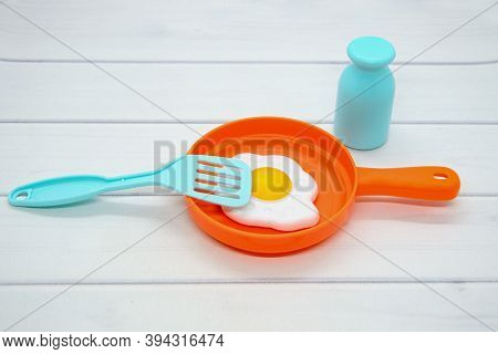 Still Life Of Children's Toy Plastic Dishes: Frying Pan With Lid, Fried Eggs, Salt Shaker, Spatula.