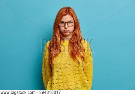 Upset Redhead Young Woman With Sulky Displeased Expression Blows Cheeks And Looks Angrily At Camera