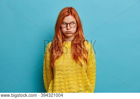 Discontent Redhead European Woman Pretends To Be Offended Blows Cheeks And Looks With Unhappy Grimac
