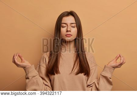 Peaceful Calm Relaxed Young Woman Meditates Indoor, Keeps Hands In Zen Gesture, Closes Eyes, Practic
