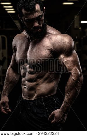 Strong Sport Athlete Male With Beard And Perfect Physique Body In Dark Fitness Gym
