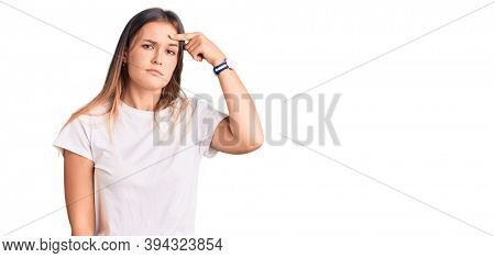 Beautiful caucasian woman wearing casual white tshirt pointing unhappy to pimple on forehead, ugly infection of blackhead. acne and skin problem