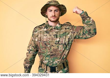 Young caucasian man wearing camouflage army uniform strong person showing arm muscle, confident and proud of power
