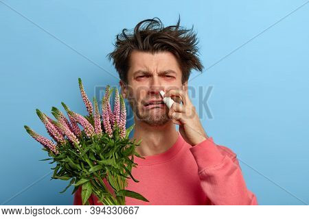Health Care And Allergy Symptoms Concept. Dissatisfied Man Cures Allergic Rhinitis With Nasal Drops,