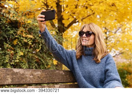 Shot Of Happy Woman Sitting On The Bench In The Park And Taking A Self Portrait. Fall Weather.