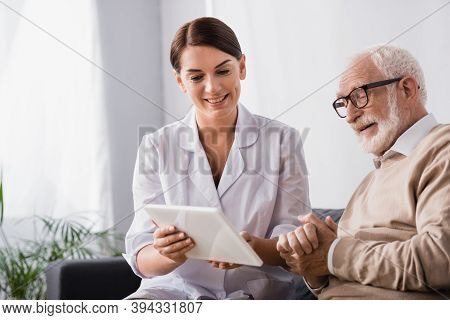 Social Worker Showing Dgital Tablet To Senior Man Sitting With Clenched Hands