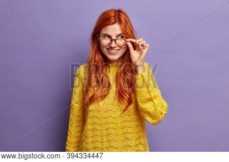 Joyful Good Looking Ginger Woman Looks Through Spectacles Wears Yellow Knitted Sweater And Poses Hap