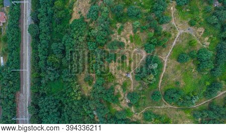 Top Down Aerial Look To Paths In Park On Hill And Train Rails On Side