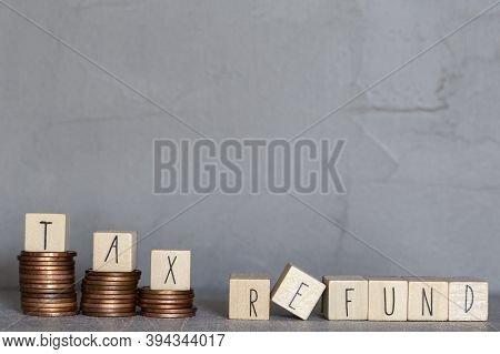 Tax Refund Text With Wooden Cubes On Concrete Modern Background Texture And Stacking Coins